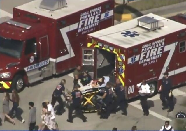 Rescue workers prepare to transport a victim on a stretcher near Marjory Stoneman Douglas High School following a shooting incident in Parkland, Florida, U.S. February 14, 2018 in this still image taken from a video