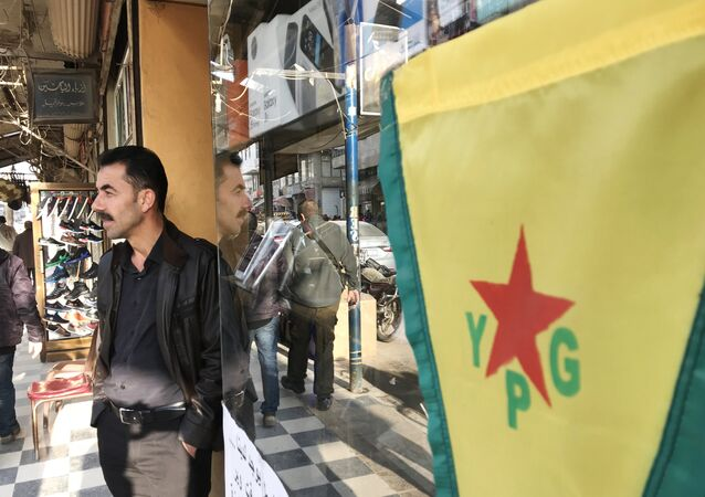 Flag of the Kurdish YPG self-defense forces on the central street of the city of Afrin, Syria