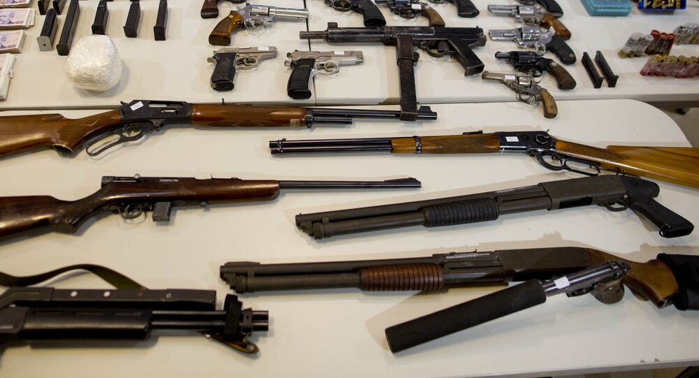 Weapons that were seized during an anti-drug raid, are displayed on a table for a media presentation in Buenos Aires, Argentina, Friday, May 16, 2014