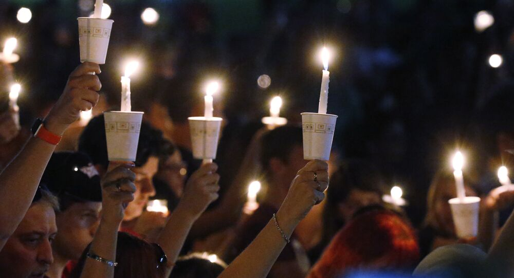 Attendees raise their candles at a candlelight vigil for the victims of the shooting at Marjory Stoneman Douglas High School, Thursday, Feb. 15, 2018, in Parkland, Fla.