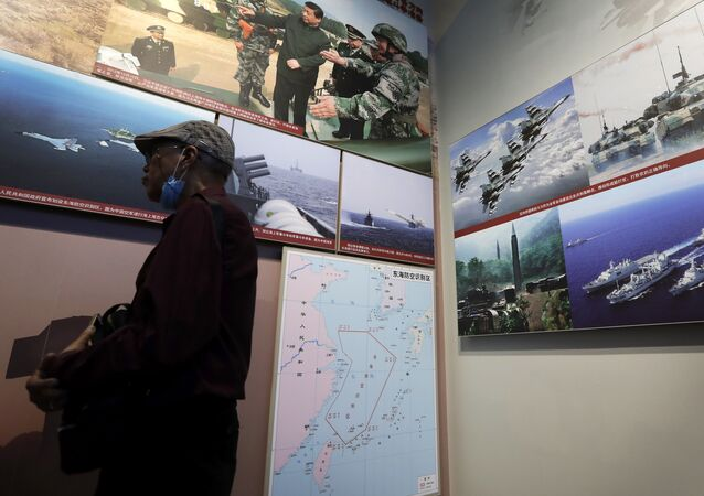 In this July 27, 2017 photo, a man walks by photos showing a map of East China Sea and Chinese military activities at East China Sea on display at the military museum in Beijing