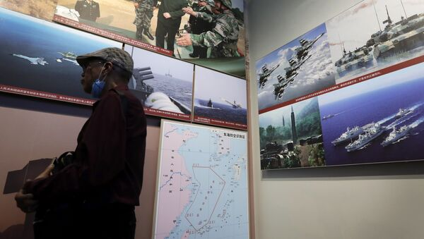 In this July 27, 2017 photo, a man walks by photos showing a map of East China Sea and Chinese military activities at East China Sea on display at the military museum in Beijing - Sputnik International