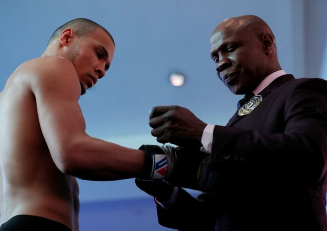 Chris Eubank junior has his gloves adjusted by his father, himself a former world champion boxer