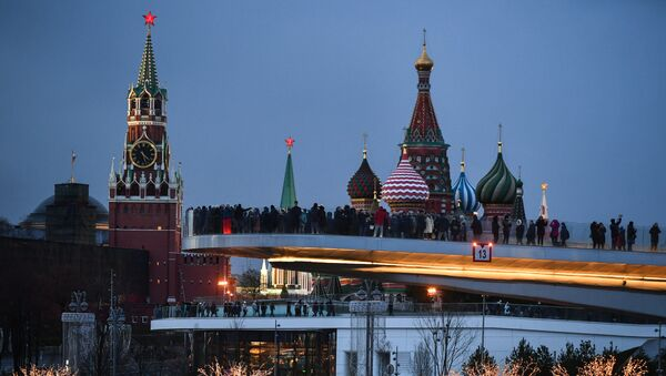 People visit Zaryadye Nature-Landscape Park in Moscow, Russia. Background from left: Spasskaya (Savior) Tower of the Moscow Kremlin and domes of Intercession of the Most Holy Theotokos on the Moat Cathedral (St. Basil's Cathedral) - Sputnik International