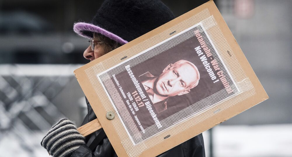 A woman holds a banner as she protests during a visit of Israeli Prime Minister Benjamin Netanyahu's at the EU headquarters in Brussels