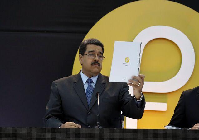 Venezuela's President Nicolas Maduro reads a document during the event launching the new Venezuelan cryptocurrency Petro in Caracas, Venezuela February 20, 2018