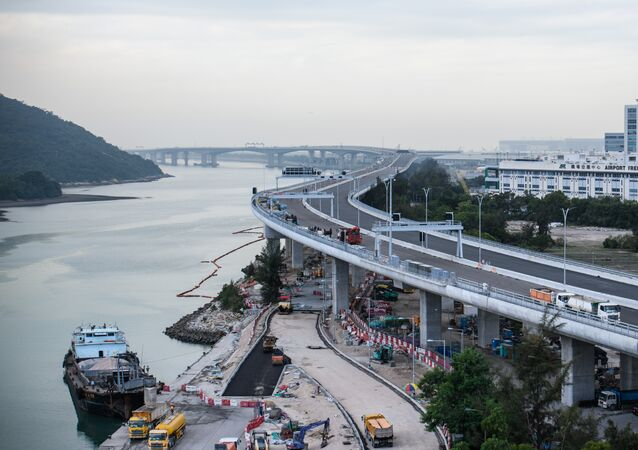 In this picture taken on November 29, 2017, a general view shows a section of the Hong Kong-Zhuhai-Macau Bridge (HKZMB) (C) that runs alongside the international airport (R) in Hong Kong
