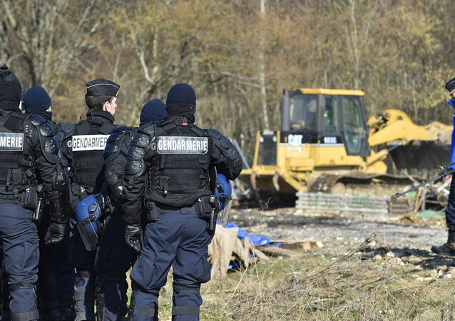 French gendarmes stand near a bulldozer being used to clear the entrance to the encampment during an operation to evacuate opponents of a nuclear waste burial site in the Lejuc woods in Bure