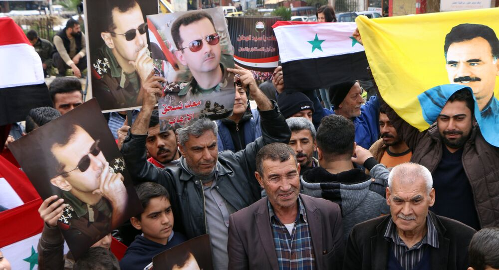 A picture taken on February 22, 2018 shows people waving the Syrian flag and portraits of President Bashar al-Assad and Kurdistan Worker's Party (PKK) leader Abdullah Ocalan as a convoy of pro-Syrian government fighters arrives in Syria's northern region of Afrin