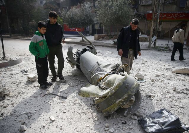 People inspect missile remains in the besieged town of Douma, in eastern Ghouta, in Damascus, Syria, February 23, 2018