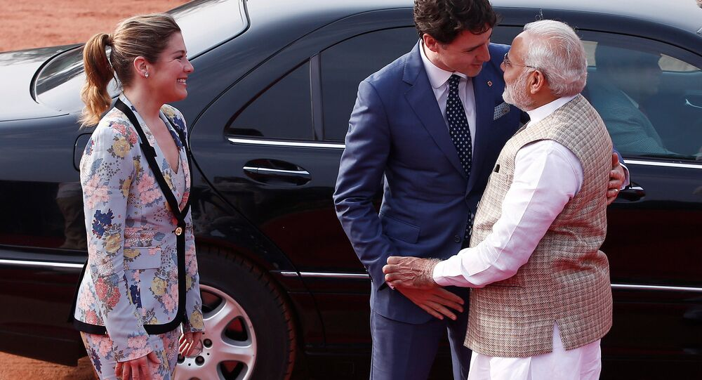 Canadian Prime Minister Justin Trudeau (C) hugs his Indian counterpart Narendra Modi as his wife Sophie Gregoire (L) looks on during Trudeau's ceremonial reception in New Delhi, India, February 23, 2018.