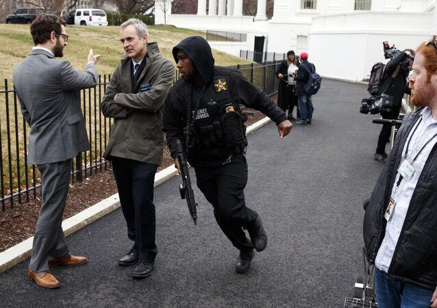 A Secret Service officer rushes past reporters after a vehicle rammed into a security barrier near the White House, Friday, Feb. 23, 2018, in Washington.