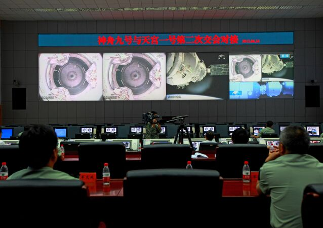 (File) Chinese technicians at the Jiuquan Space Centre monitor the Shenzhou-9 spacecraft as it prepares to link with the Tiangong-1 module just over a week into a manned space mission which includes China's first female astronaut, following an automatic docking, on June 24, 2012