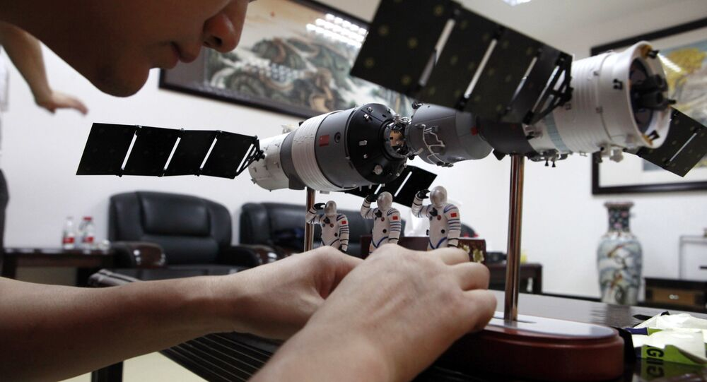 A Chinese official arranges astronaut figures with a scale model of the Shenzhou 9 module docking with China's Tiangong 1 space module to present them at a press conference at the Jiuquan satellite launch center near Jiuquan in western China's Gansu province, Friday, June 15, 2012