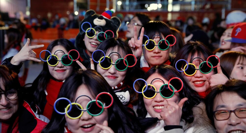 Volunteers wearing Olympic rings shaped sunglasses pose for photographs during a medal ceremony at the Medal Plaza in Pyeongchang, South Korea, February 18, 2018. Picture taken on February 18, 2018