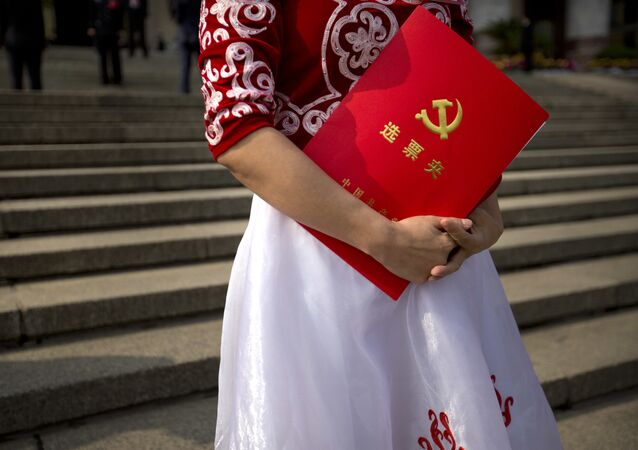 A delegate holds her ballot folder after the closing ceremony of China's 19th Party Congress at the Great Hall of the People in Beijing, Tuesday, Oct. 24, 2017
