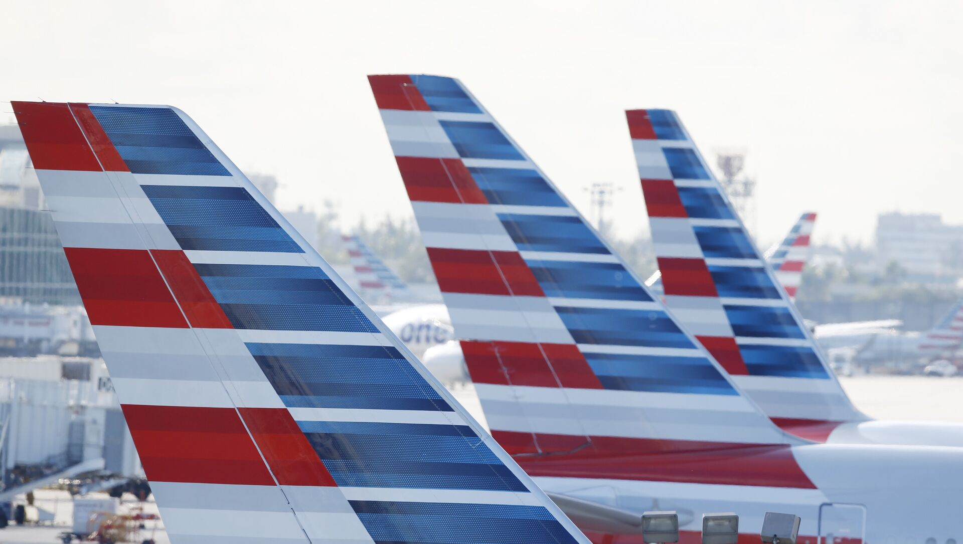 Painted vertical stabilizers are viewed as American Airlines jets are parked on the airport apron, Monday, Nov. 6, 2017, at Miami International Airport in Miami. American Airlines and a subsidiary will pay $9.8 million in stock to settle claims that they failed to help disabled employees return to work. - Sputnik International, 1920, 26.07.2021