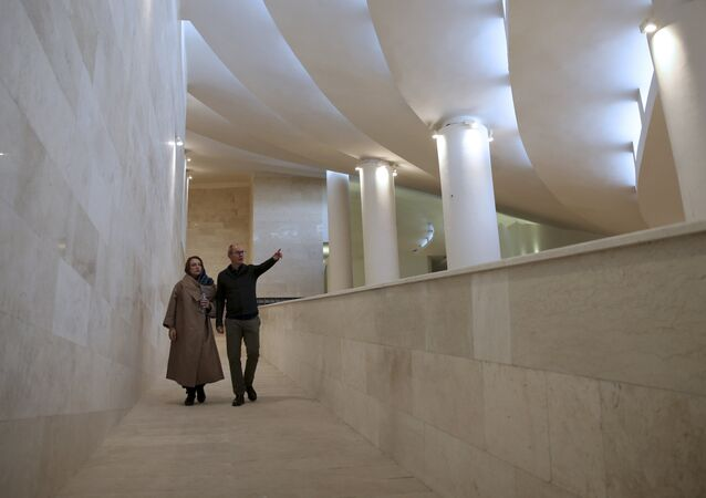 In this Wednesday, Feb. 7, 2018, photo, Reza Daneshmir, right, gestures as he talks with his wife Catherine Spiridonoff, both architects of Vali-e-Asr mosque, while they walk on one of the mosque's ramps, in Tehran, Iran
