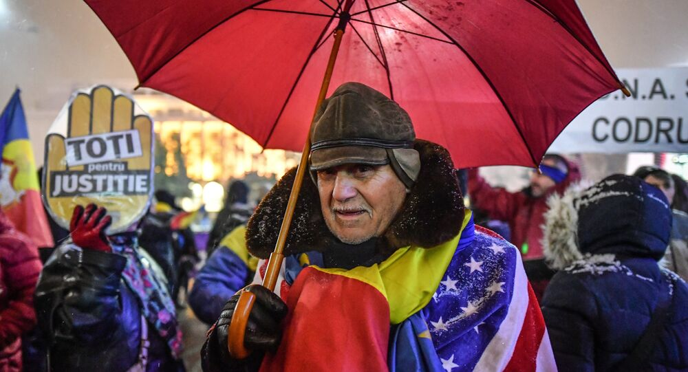 A man wear Romanian and US flags during a protest against the Justice minister and the corruption in front of the Romanian Government in Bucharest