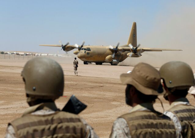 Saudi soldiers watch as a Saudi military cargo plane lands to deliver aid at an airfield in Marib, Yemen January 26, 2018