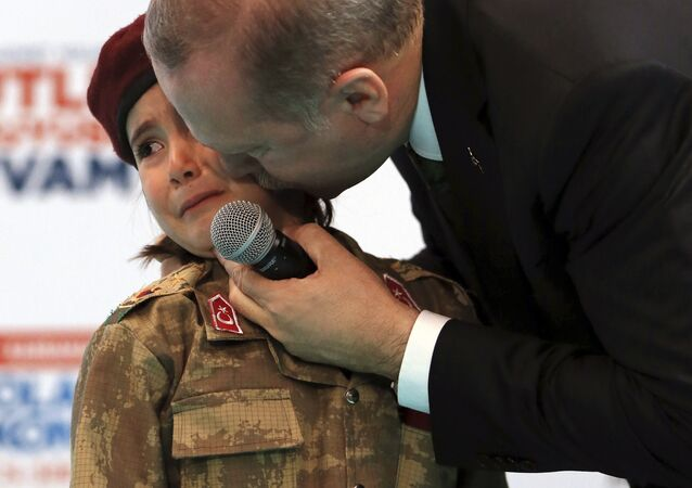 FILE - In this Saturday, Feb. 24, 2018 file photo, Turkish President Recep Tayyip Erdogan kisses Amine Tiras, a young girl in military uniform as he speaks to his ruling party members, in Kahramanmaras, Turkey