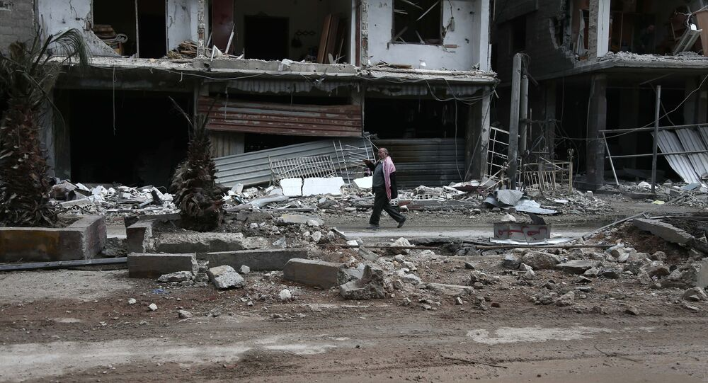 A Syrian man walks past destroyed buildings in the rebel-held town of Haza, in the besieged Eastern Ghouta region on the outskirts of the capital Damascus