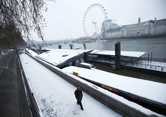 A man walks through the snow on the Embankment in London, Britain, March 1, 2018
