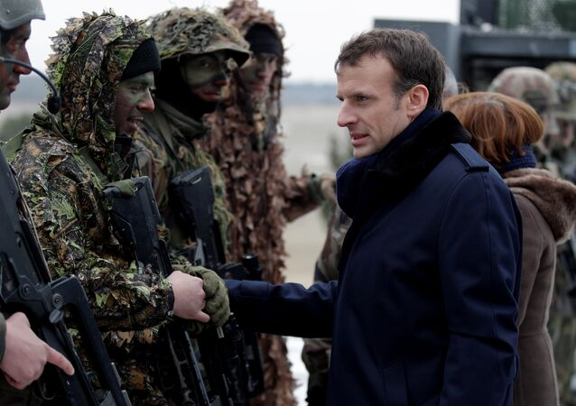 French President Emmanuel Macron speaks with soldiers wearing camouflage as he attends a military exercise at the military camp of Suippes, near Reims, France, March 1, 2018