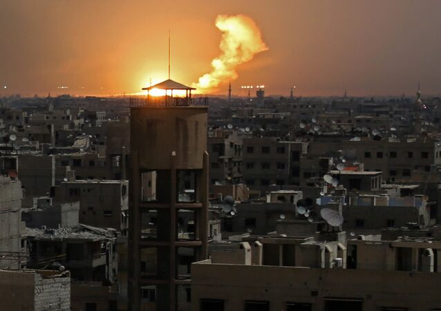 A picture taken on February 28, 2018 shows flames erupting in the horizon following a reported rocket attack in al-Shaffuniyah, in the enclave of Eastern Ghouta on the outskirts of the Syrian capital Damascus