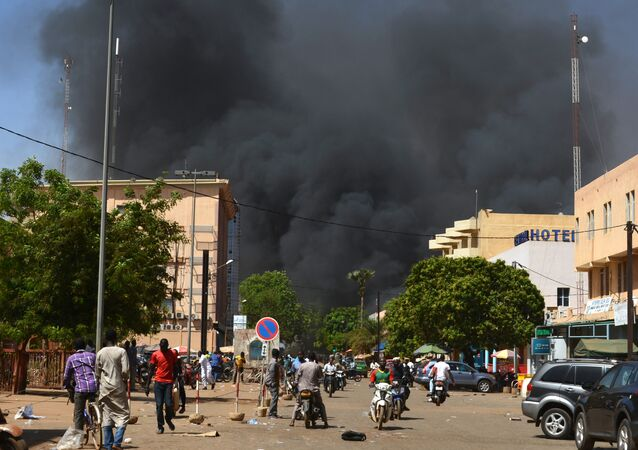 People watch as black smoke rises as the capital of Burkina Faso came under multiple attacks on March 2, 2018, targeting the French embassy, the French cultural centre and the country's military headquarters