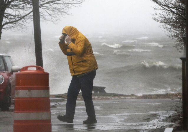 A pedestrian walks near the coastline Friday, March 2, 2018, in Newburyport, Mass. as a major nor'easter pounds the East Coast, packing heavy rain, intermittent snow and strong winds.