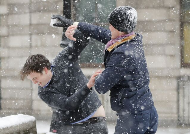 Employess have a snow fight outside the Bank of England in central London on March 2, 2018