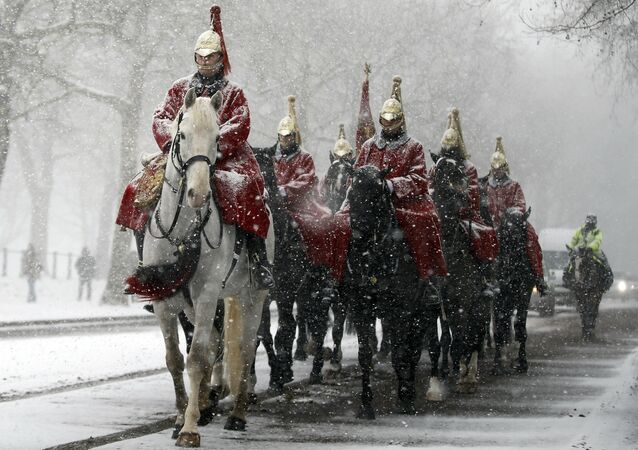 Members of the Household Cavalry return to their barracks as snow falls in London, Wednesday, Feb. 28, 2018