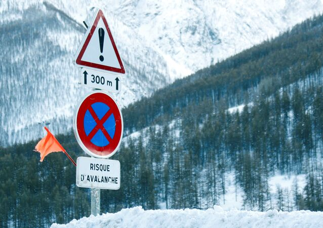 Road signs are pictured on a snow-covered road in Saint-Pancrace as winter weather bringing snow and freezing temperatures continues in France, March 2, 2018. The sign reads, Avalanche risk
