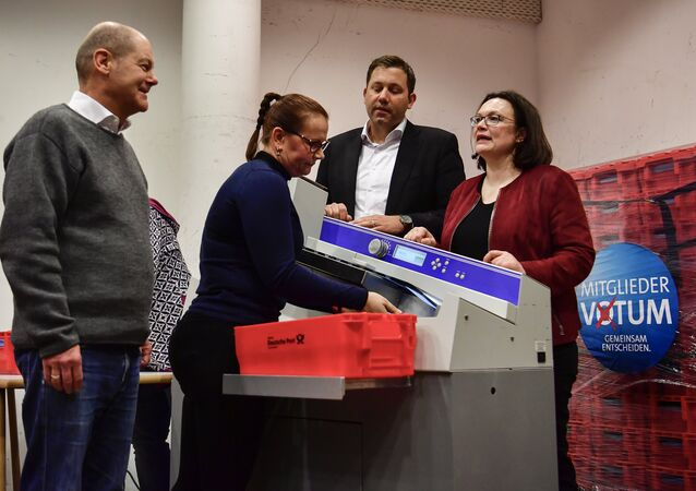 Acting Chairman of the Social Democratic Party (SPD) Olaf Scholz (L), Secretary-General of the Social Democratic Party (SPD) Lars Klingbeil (2nd R) and German Labour and Social Minister Andrea Nahles (R) react as they look at an envelope opening machine prior to the counting of the ballots, at the headquarters of Germany's social democratic SPD party in Berlin on March 3, 2018, as SPD members voted on whether or not to join a new coalition government with German Chancellor Angela Merkel's conservatives