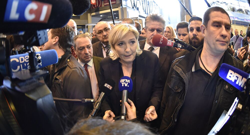 French far-right Front National (FN) party president Marine Le Pen (C), speaks to journalists as she visits the 55th International Agriculture Fair (Salon de l'Agriculture) at the Porte de Versailles exhibition center on February 28, 2018 in Paris