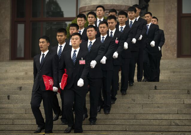 Security officials march in formation as they leave after the opening session of the Chinese People's Political Consultative Conference (CPPCC) held in Beijing's Great Hall of the People, Saturday, March 3, 2018.