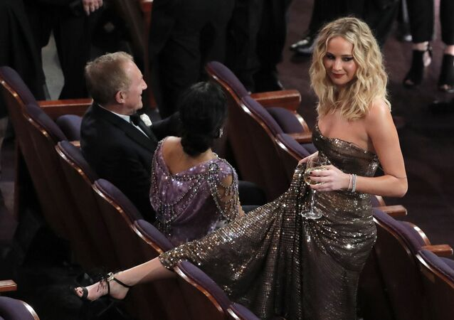 90th Academy Awards - Oscars Show - Hollywood, California, U.S., 04/03/2018 - (L-R) Salma Hayek and her husband Francois-Henri Pinault sit as Jennifer Lawrence stands