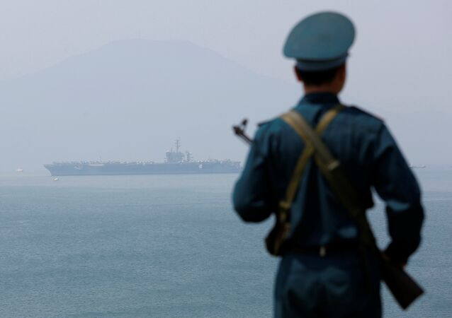 A Vietnamese soldier keeps watch in front of U.S. aircraft carrier USS Carl Vinson after its arrival at a port in Danang, Vietnam March 5, 2018