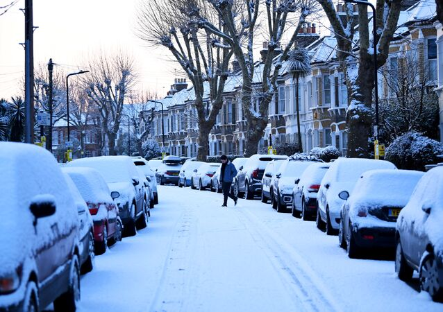 A man walks down a snow covered street in South London, Britain, February 28, 2018