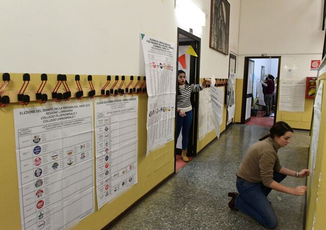 Women post electoral posters at a polling station on March 3, 2018 in Milan
