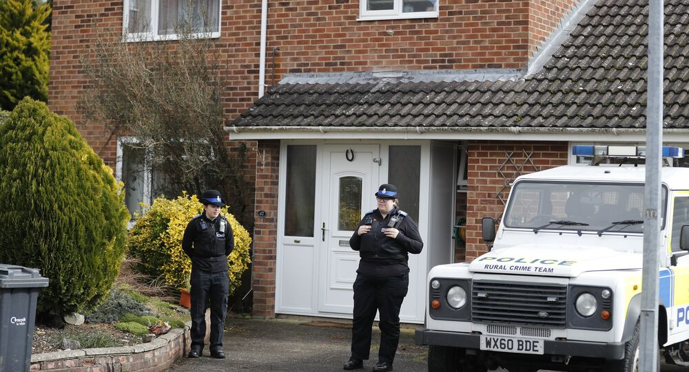 Police officers stand outside the house of former Russian double agent Sergei Skripal who was found critically ill Sunday following exposure to an unknown substance in Salisbury, England, Tuesday, March 6, 2018