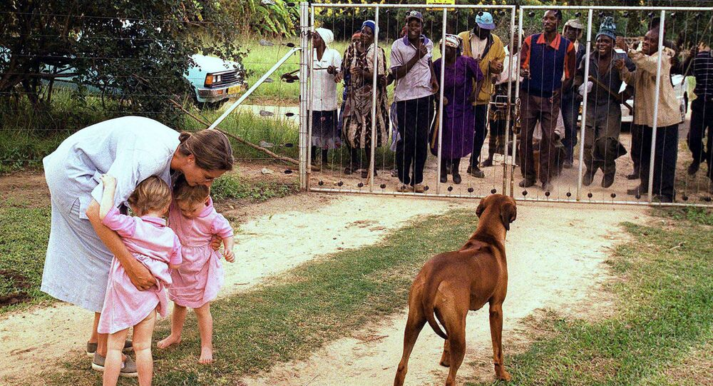 In this file photo dated March 29, 2000, Pippa van Rechteren, left, and her two-year-old twins Catherine, second from left, and Elisabeth, third from left, are blocked from leaving their house on the white-owned commercial farm, Chiripiro, by Zimbabwe war veterans in Centenary district, 150 kilometers (93 miles) north of Harare