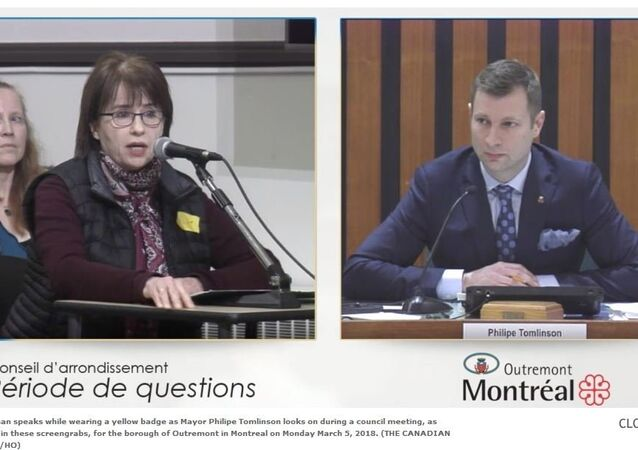 A woman speaks while wearing a yellow badge as Mayor Philipe Tomlinson looks on during a council meeting, as shown in these screengrabs, for the borough of Outremont in Montreal on Monday March 5, 2018
