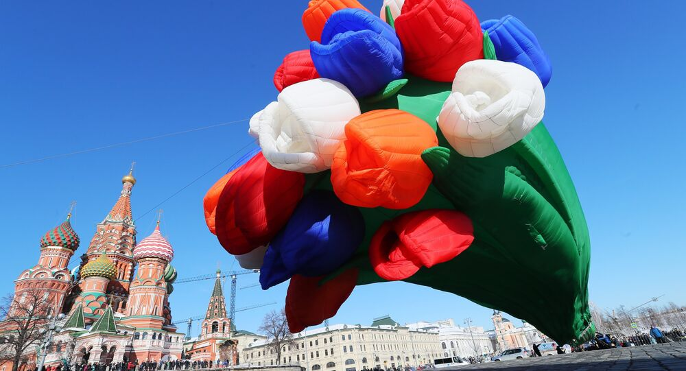 An air balloon shaped as a bunch of tulips drifts over Vasilyevsky Spusk Square, Moscow