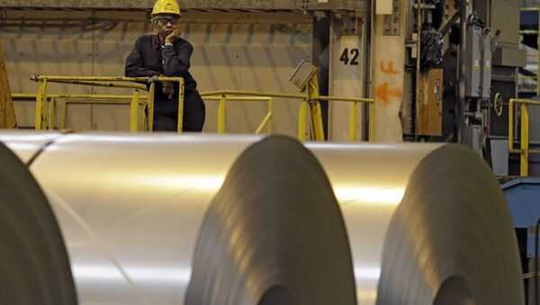 An employee looks on from behind coils of steel as acting Secretary of Labor Seth Harris speaks to workers after a tour of ArcelorMittal Steel's hot dip galvanizing line in Cuyahoga Heights, Ohio (File) - Sputnik International