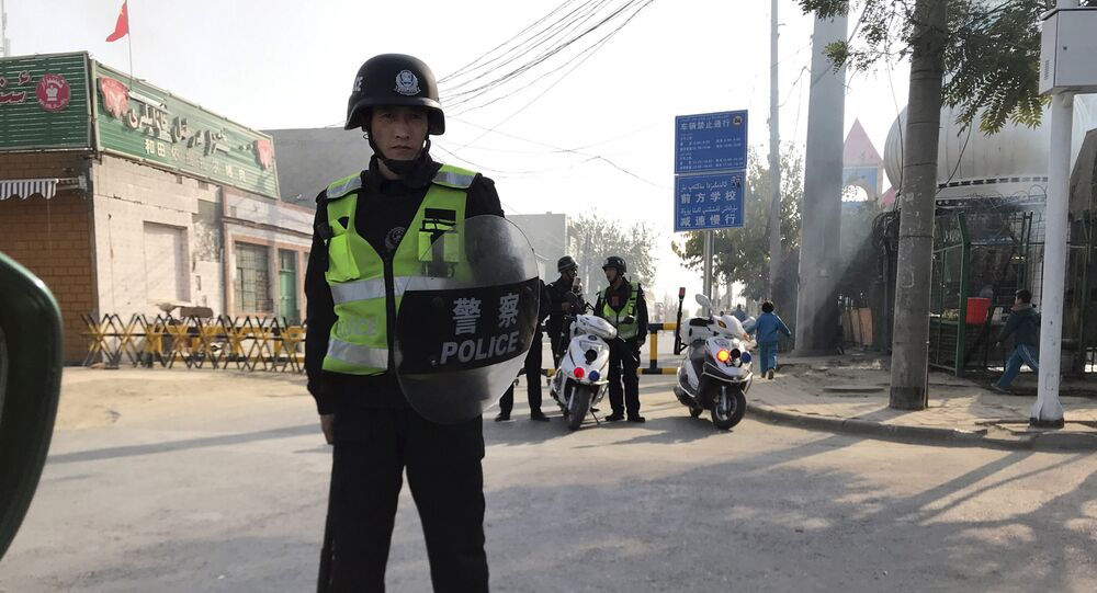 (File) In this Nov. 2, 2017 photo, a police personnel holding shield and baton guards a security post leading into a center believed to be used for re-education in Korla in western China's Xinjiang region