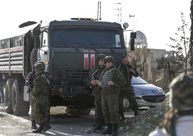 Russian military police officers stand by a troop carrier at a newly-opened crossing in the southern tip of the rebel-held Eastern Ghouta enclave linking the town of Jisreen to the government-controlled suburbs of the capital Damascus on March 8, 2018