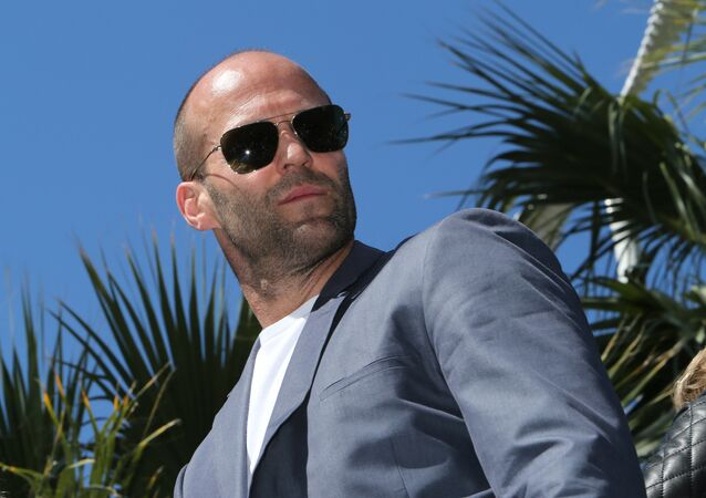 British actor Jason Statham poses on a tank as he arrives for a photocall for the film The Expendables 3 at the 67th edition of the Cannes Film Festival in Cannes, southern France, on May 18, 2014