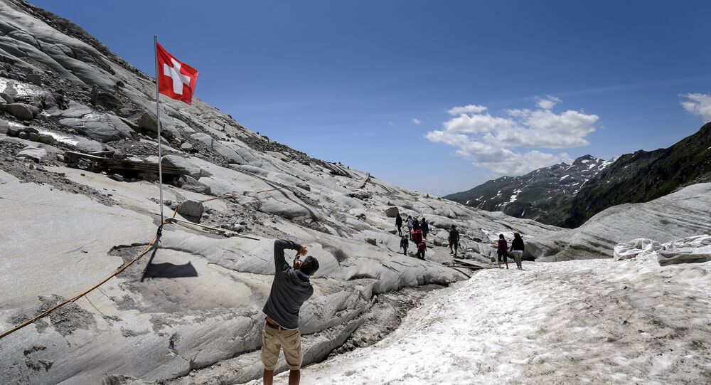 A tourist takes a picture of a Swiss flag on the Rhone Glacier covered with insulating foam to be protected from the sun on July 14, 2015, near Gletsch